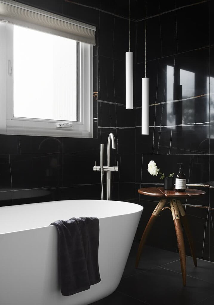 A dramatic black bathroom with a white bath and wooden table